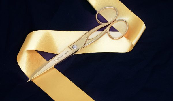 Gold plated scissor on a golden ribbon