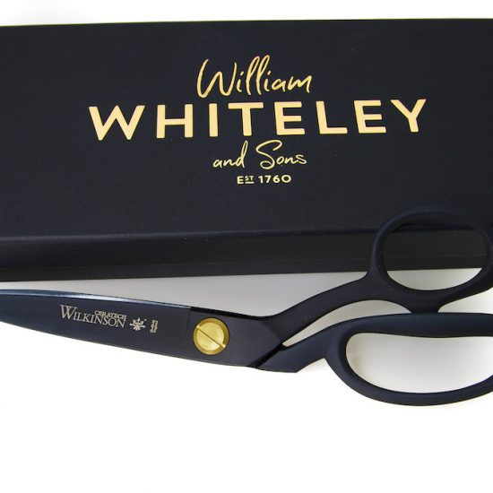 The scissor beside it's elegant black gift box with gold lettering