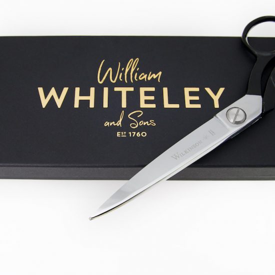 The scissor in front of an elegant black box with gold lettering