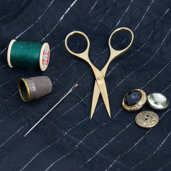 A picture of the gold plated embroidery with a vintage thimble, needle and buttons next to green thread on a pinstriped silk background.