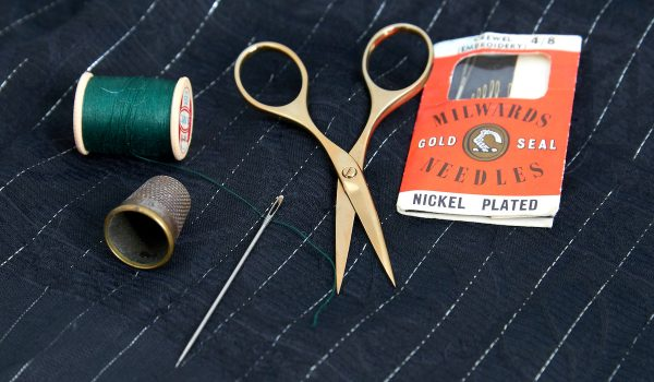 A picture of the gold plated embroidery scissors on pinstriped silk, with a vintage thimble, a pack of vintage sewing needles and green thread.