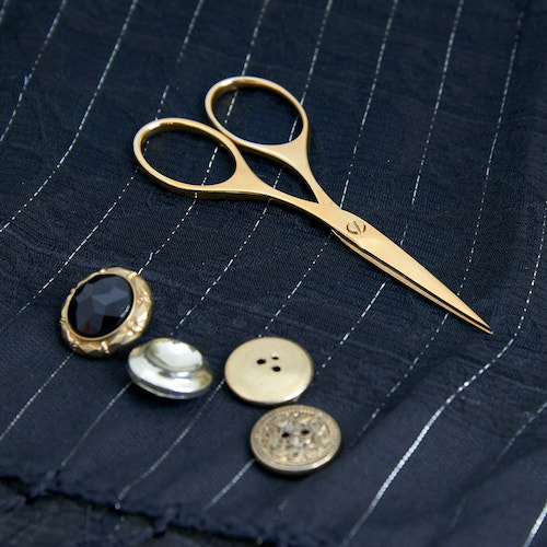 A picture of the gold plated embroidery scissor on pinstriped silk next to vintage buttons.