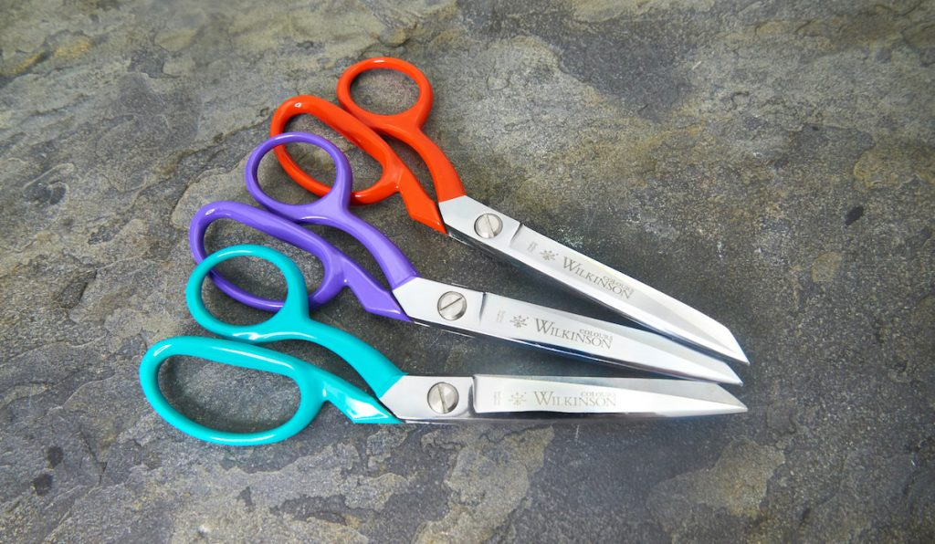 Wilkinson colours scissors in teal, purple and red on grey slate